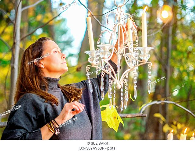 Mature woman lighting chandelier candle in woods