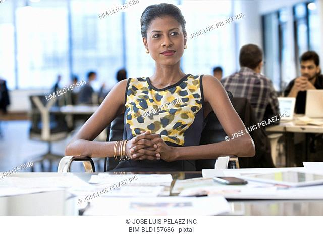Pensive mixed race businesswoman sitting at desk in office