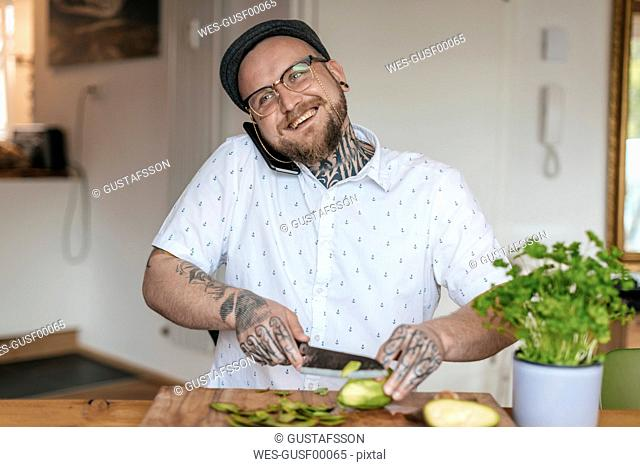 Smiling man on the phone chopping vegetables in the kitchen