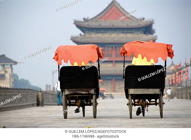 Rickshaw drivers carrying tourists on top of the Xian City Wall, Xian, Shaanxi Province, China