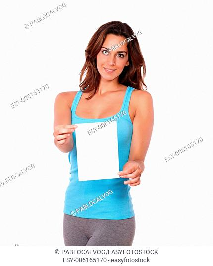 A portrait of a beautiful girl on blue gym clothing standing and holding a blank card of cpoyspace while looking at you on isolated background