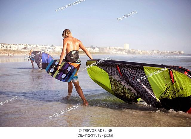 Man dragging kiteboarding equipment into ocean surf