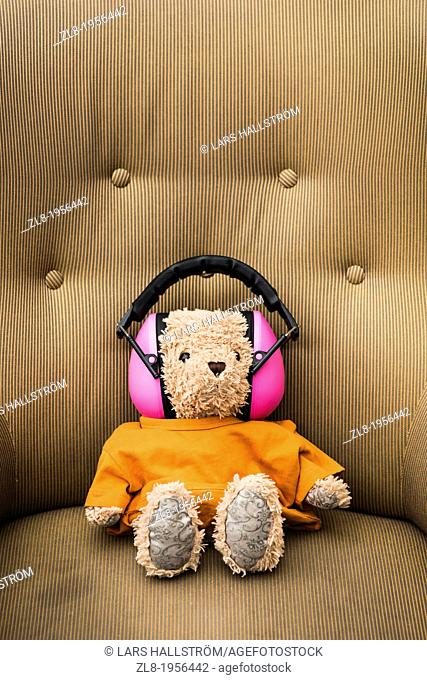 Conceptual image of teddybear wearing orange sweater and pink hearing protection sitting in armchair