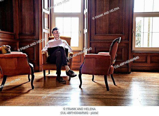 Businessman sitting in ornate room