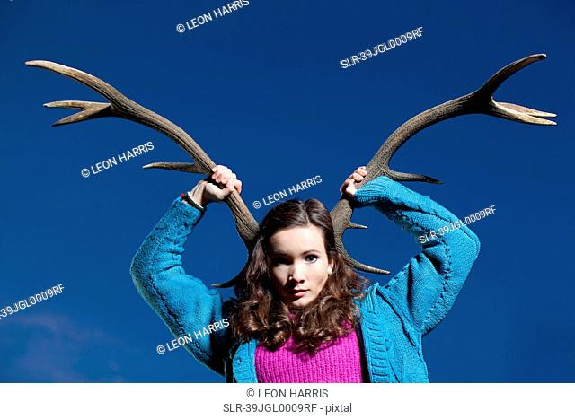 Woman holding antlers on head