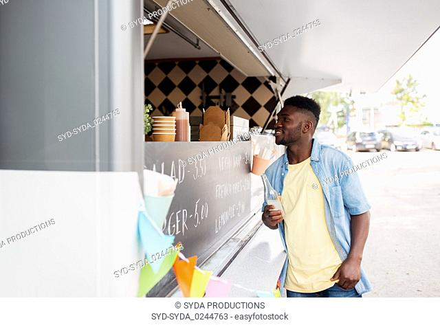 african american man with drink at food truck