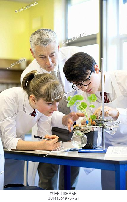 Teacher helping high school students conducting scientific experiment in biology class