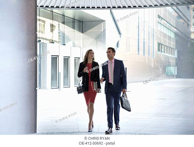 Corporate businessman and businesswoman walking outside building