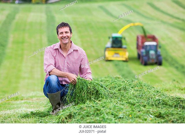 Portrait of smiling farmer in field next to green hay