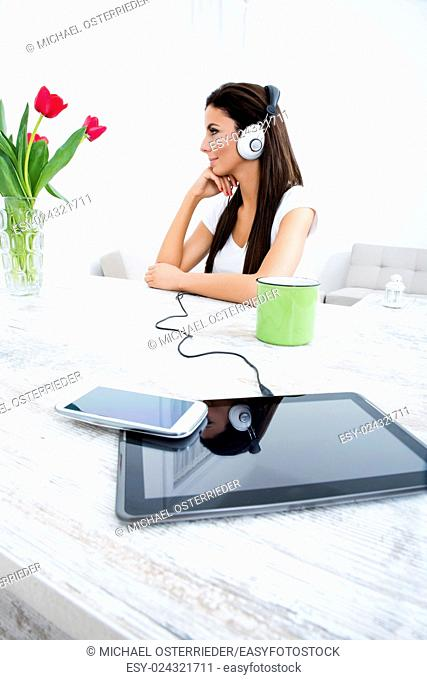 Portrait of a young beautiful woman listening to music with headphones