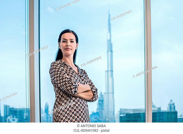 Portrait of businesswoman at window, Dubai, United Arab Emirates