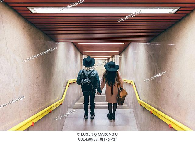 Young couple in stairwell, elevated view, rear view