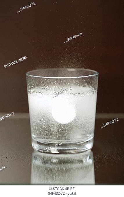 Glass of water with a sparkling pill in it, close-up, high angle view
