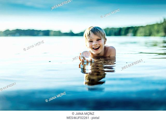 Portrait of happy boy in a lake holding tansparent sphere
