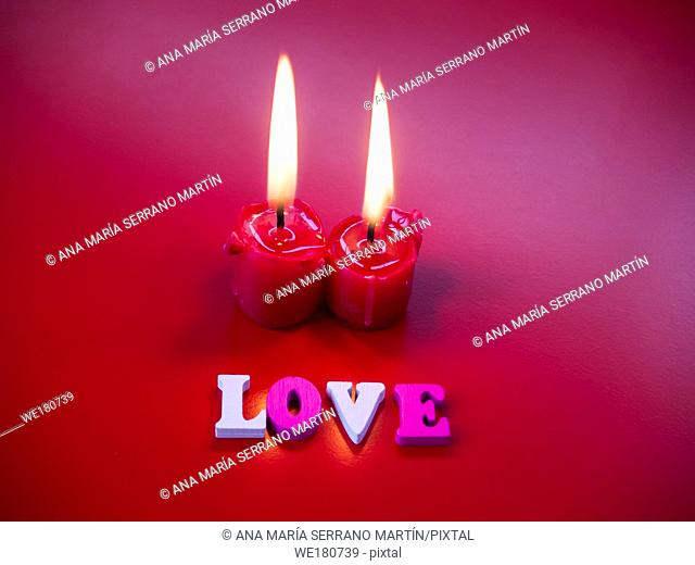 Concept of love Red candles lit and the word love with a red background