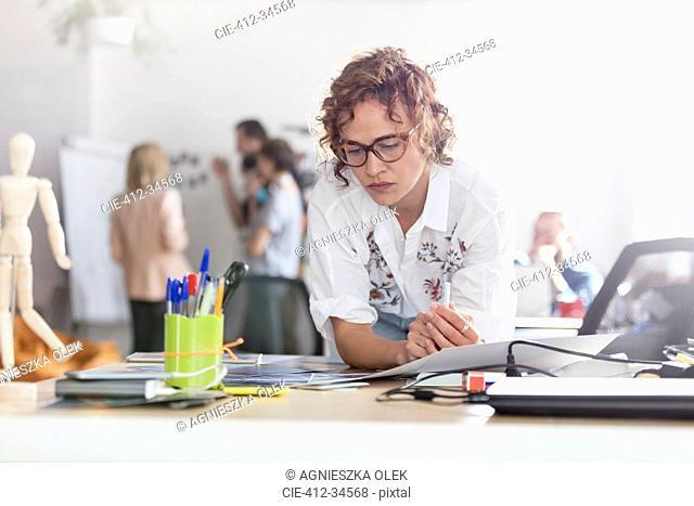 Focused female design professional planning in office