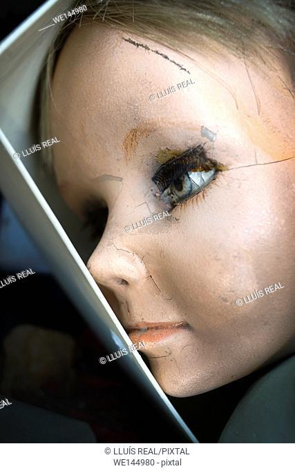 Primer plano de una cabeza de muñeca de porcelana desde el interior de una caja. , Close up of a porcelain doll head from inside a box