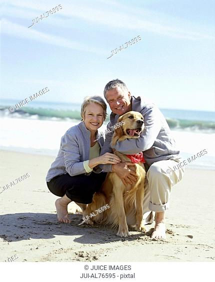 View of a couple playing with their dog on the beach