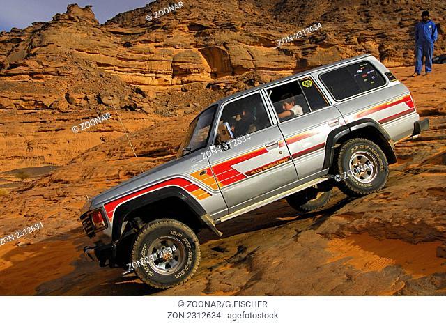 Geschicklichkeitstest für den Fahrer eines Geländefahrzeug mit Touristen in einer steilen Felspassage, Akkakus-Gebirge, Sahara