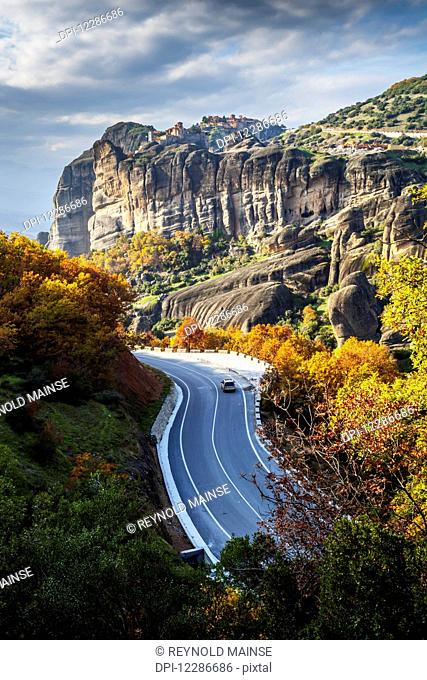 Monasteries perched on cliffs and a winding road in autumn foliage; Meteora, Greece