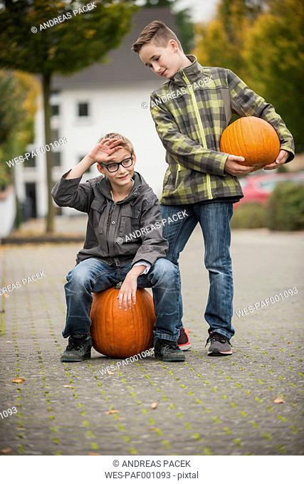 Two boys with two big pumpkins