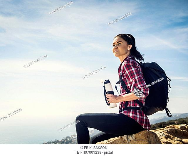 Woman with water bottle sitting on rock
