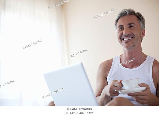Smiling man drinking coffee and using laptop in bedroom