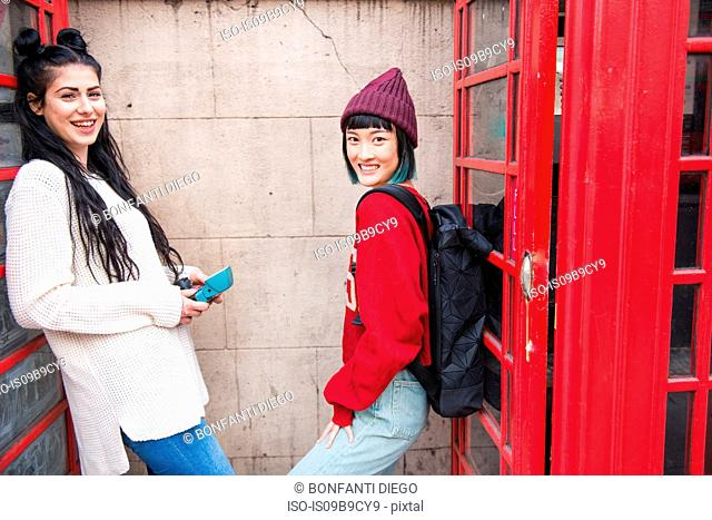Portrait of two young stylish women leaning against red phone boxes, London, UK