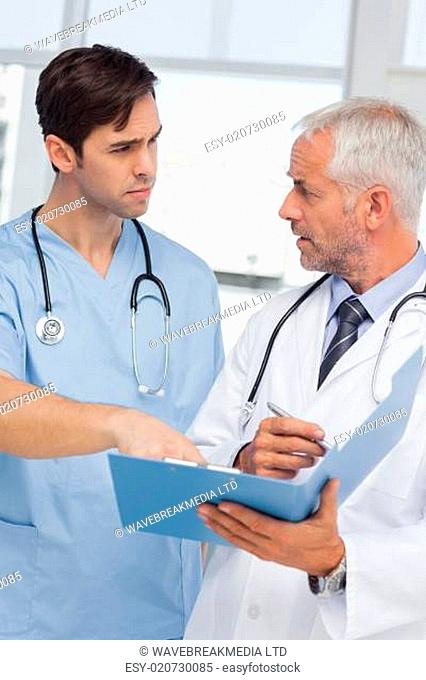 Serious doctors talking about file in hospital