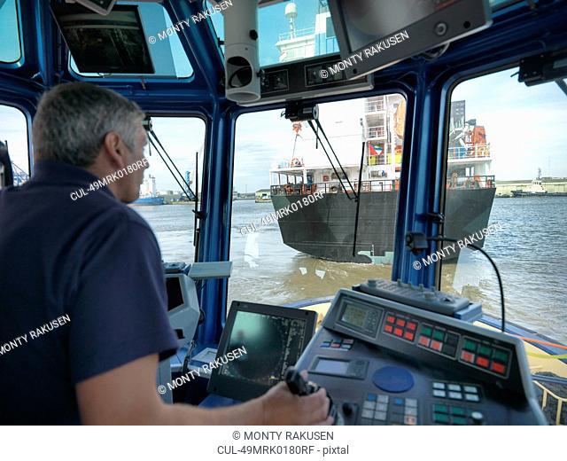 Captain steering tugboat in wheelhouse