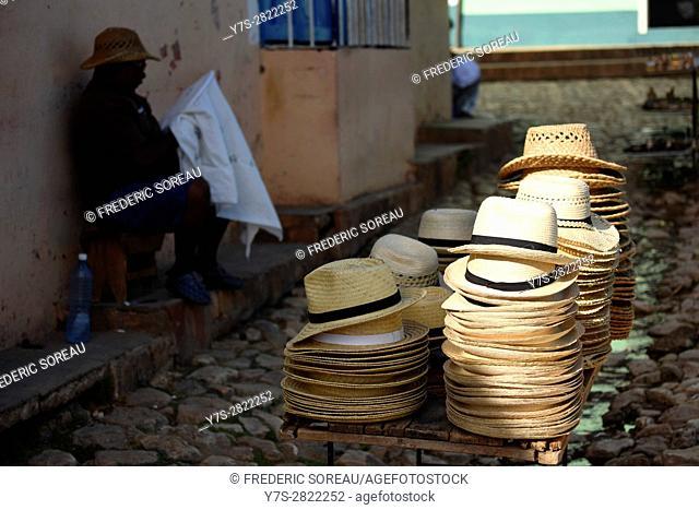 Cuban man saling straw hat in Trinidad street market, Cuba
