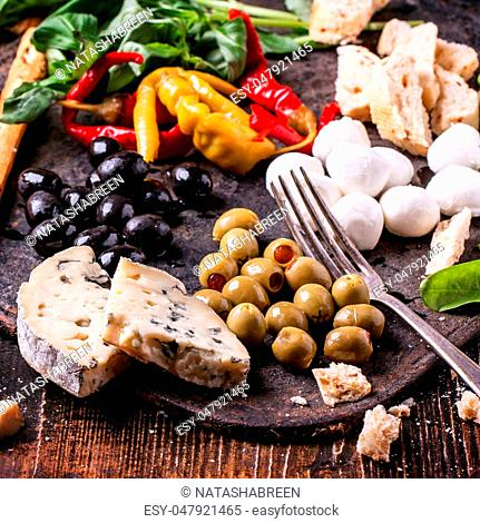Mixed antipasti pickled blue cheese, olives and mozzarella served on cast-iron board over wooden table with vintage fork
