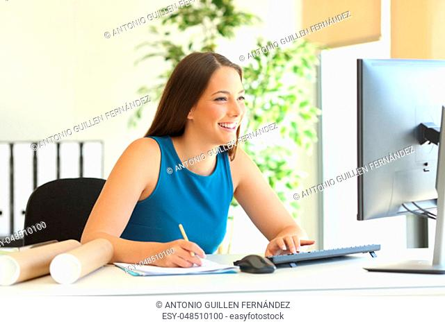 Happy businesswoman working on line with a computer and taking notes at office