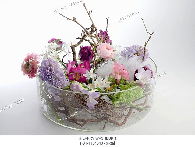 A glass bowel vase with an arrangement of various flowers