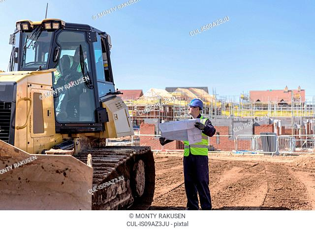 Builder with site plans in discussion with bulldozer driver on housing building site