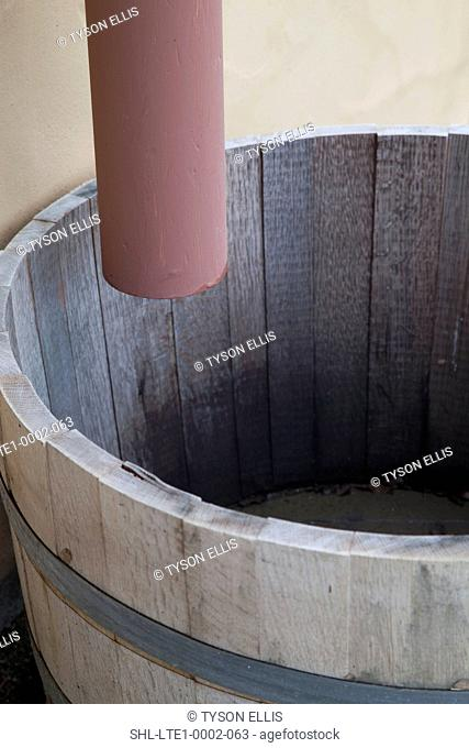 Drain pipe dripping into wooden barrel