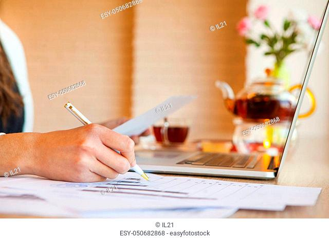 Female hands writing pen in white case on paper. Open laptop, teapot with tea fueled by candle, little cup honey, full cup tea and yellow vase with flower...