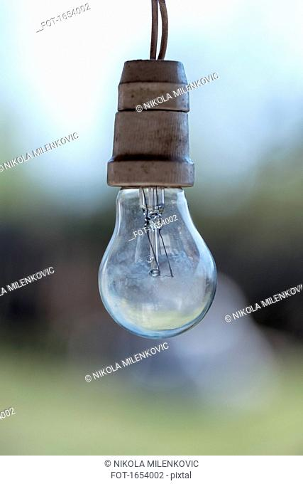 Close-up of light bulb hanging outdoors