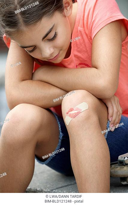 Caucasian girl with lipstick kiss over bandage on knee