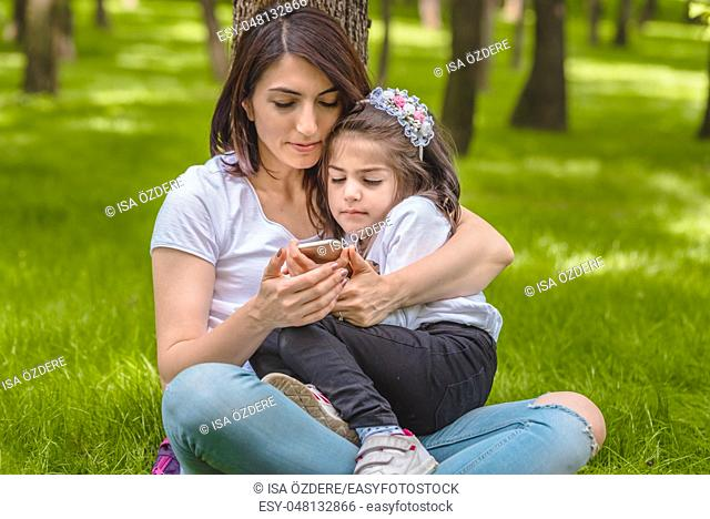 Young mom and little girl look at photos at smart phone after take selfie. Happy mother and daughter moments with love and natural emotion