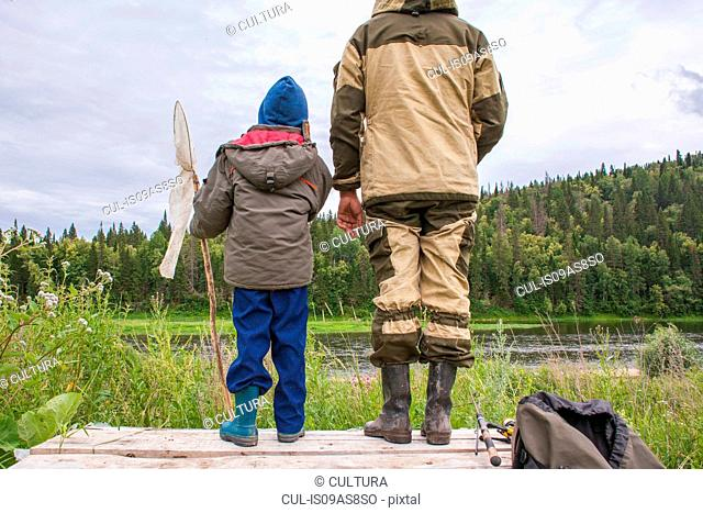 Father and son standing on jetty with fishing equipment, rear view