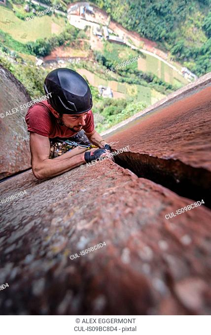 Rock climber climbing sandstone rock, overhead view, Liming, Yunnan Province, China