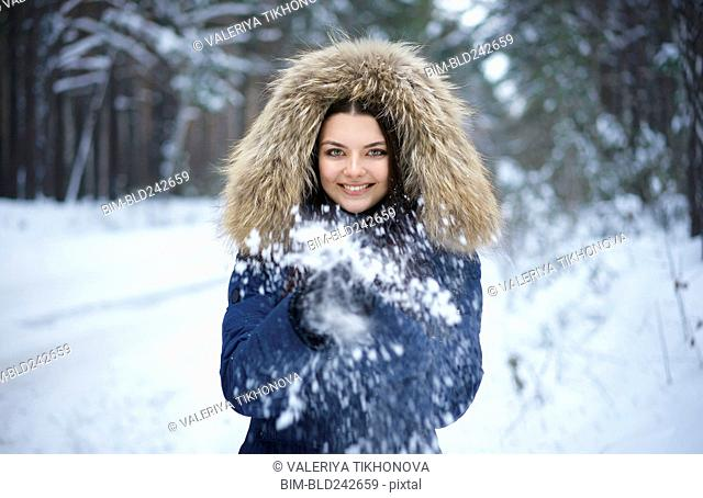 Portrait of playful Caucasian woman throwing snow