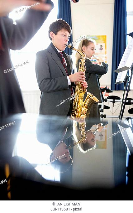 High school student playing saxophone in music class