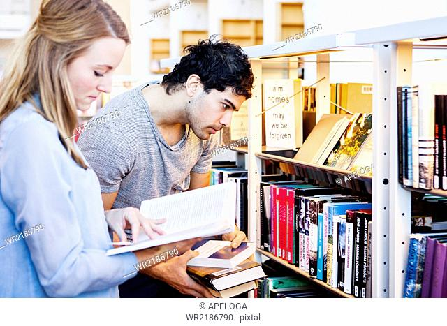 Young man choosing books while friend reading it in library