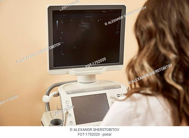 Rear view of medical worker using ultrasound machine at hospital