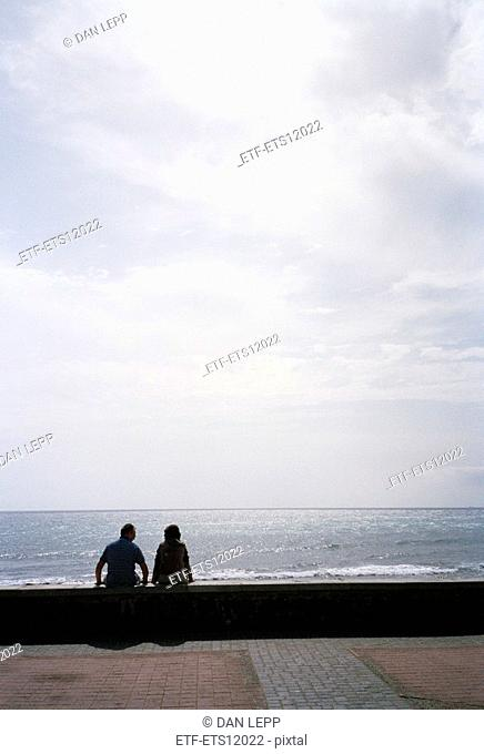 A couple sitting on a wall by the ocean Meloneras The Canary Islands Spain