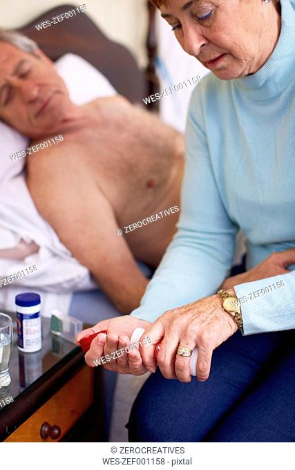 Senior woman caring for sick husband at home