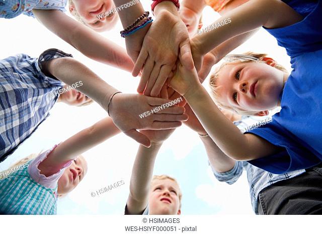 Germany, Bavaria, Group of children putting hands together