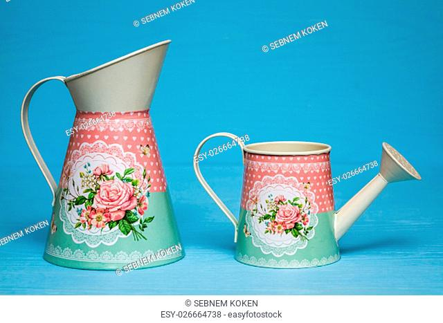 Simple colorful metallic watering cans on blue background